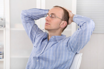 Mittags im Büro: Mann entspannt sich und schläft im Job