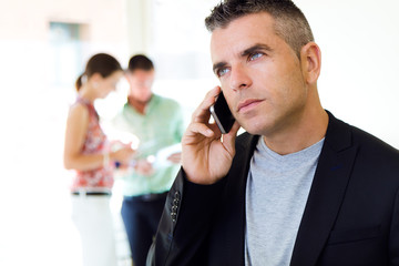 Businessman talking on mobile phone in office.