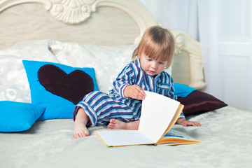 Little boy reading book on the bed