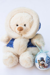 White Teddy Bear in a Winter Coat and a Christmas Tree Ball with