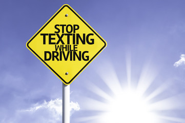 Stop Texting While Driving road sign with sun background
