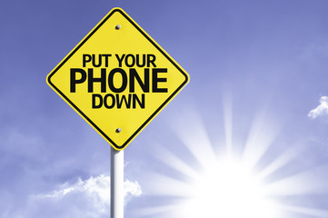 Put Your Phone Down road sign with sun background