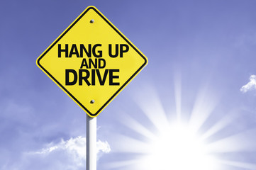 Hang Up and Drive road sign with sun background