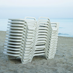Pile of white lounging chairs
