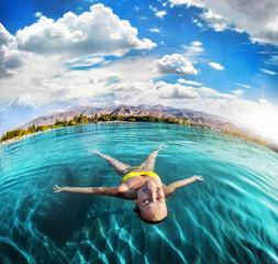 Woman swimming in the mountain lake