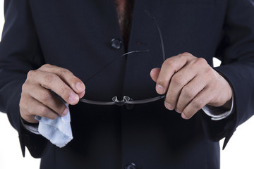 Hands of businessman cleaning glasses