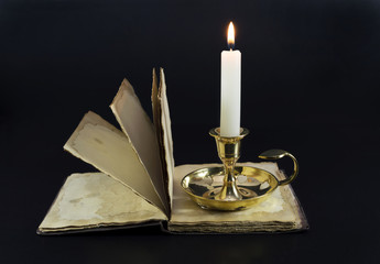 Burning candle and the open book