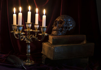 Mystic still life with skull, candles and books