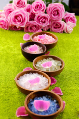 salt with flower petals in bowl, branch rose on green soft towel