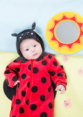 Pretty baby girl, dressed in ladybug costume on green background