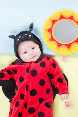 Pretty baby girl, dressed in ladybug costume on green