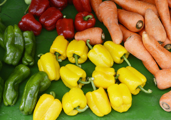 Red, green and yellow sweet bell peppers, fresh carrots on leaf