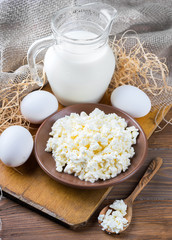 Milk and fresh eggs on a wooden board