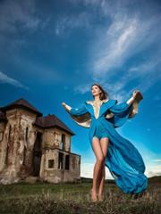 Fashionable beautiful young woman in long blue dress near castle