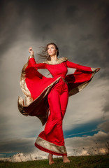 Fashionable beautiful young woman in red long dress in storm