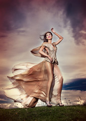 Fashionable beautiful young woman against cloudy dramatic sky