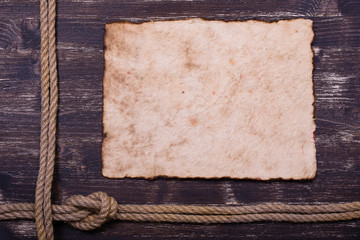 Old burnt paper on wood with rope frame background