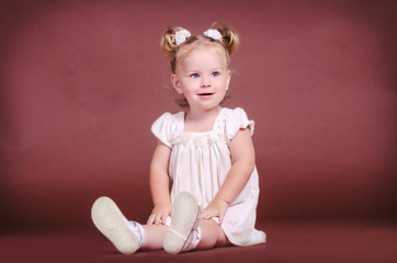 funny lovely baby girl little child in white dress. happy blonde