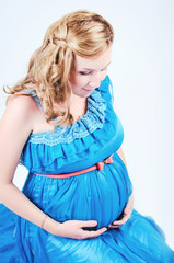 Beautiful pregnant woman in studio. Blonde pregnant woman on whi