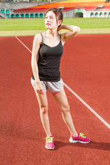 Chinese female athelete stretching on sports field