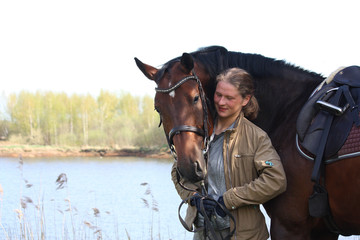 Young woman and brown horse together on the river coast
