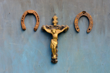 Suffering of Jesus Christ and  horseshoe on blue wooden wall