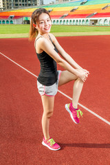Chinese female athelete stretching legs on sports field, warming