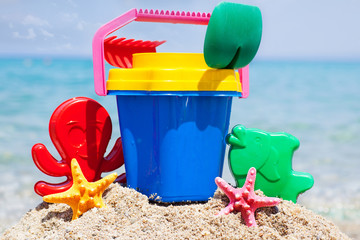 Child's bucket, spade and other toys on tropical beach against b