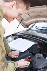 Mechanic reading instructions manual and replacing broken part