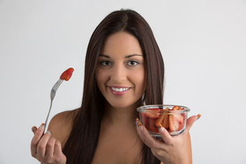 Pretty woman with a bowl full of strawberries in her hand