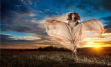 Fashionable beautiful woman looking as a butterfly in sunset