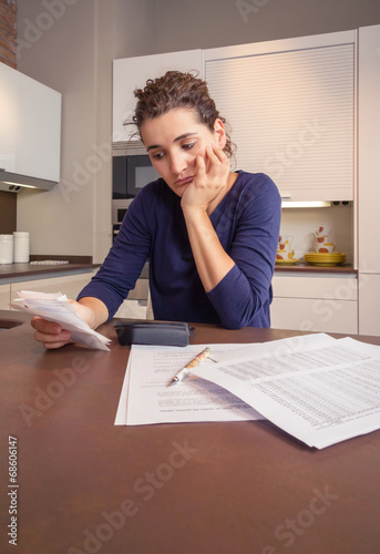 Unemployed and divorced woman with debts reviewing her monthly