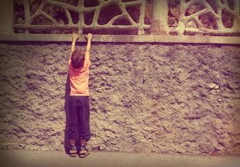Kind turnt an einer Mauer