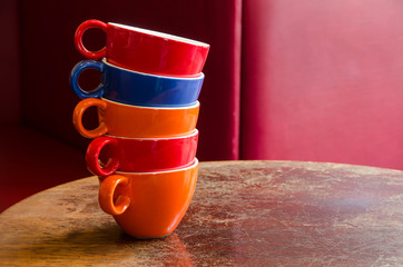 colorful coffee cups stacked on an old wooden table in a cafe