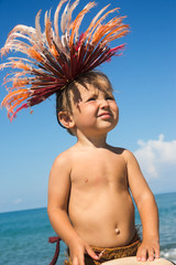Baby boy in African feathers on head on sea coast