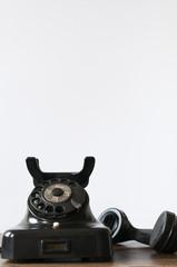 Altes Telefon vor weissem Hintergrund fuer Textfreiraum