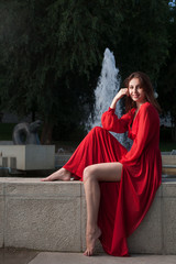 Young women in red vintage dress sitting on fountain