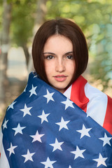 Happy young woman warp in US american flag