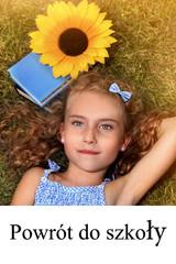 Uczennica - dzieczynka leży na trawie z kasiążką