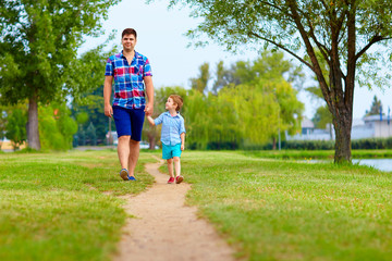father and son walking together in park