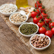 Legumes in bowls, tomatoes, garlic and olive oil on wooden table