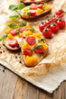 Tasty bruschetta with tomatoes, on old wooden table