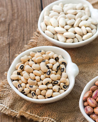 Assortment of legumes in bowls on wooden table