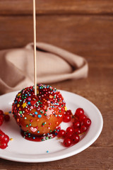 Sweet caramel apple on stick with berries, on wooden table
