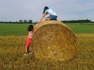 Enfants jouant sur un ballot de foin à la campagne