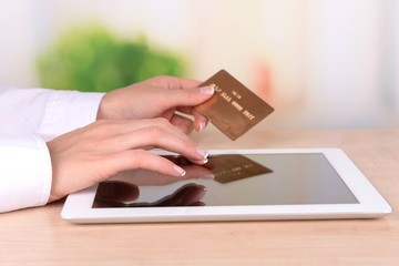 Female hands holding credit card and computer tablet