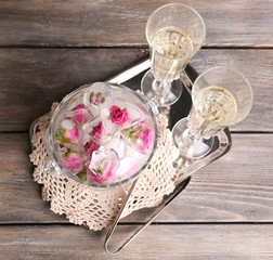 Ice cubes with rose flowers in glass bucket and two glasses
