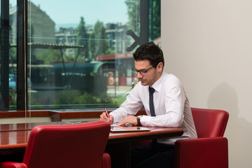 Portrait Of Attractive Businessman Reading Paper In Office