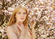 Obrazy na płótnie, fototapety, zdjęcia, fotoobrazy drukowane : Young blond woman smelling flowers