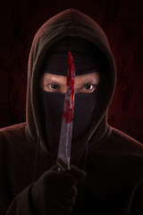 Murderer posing with bloody knife